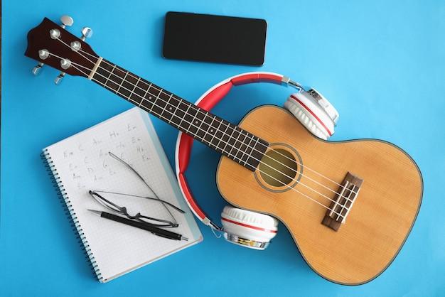 Гитара с наушниками, смартфонами и ноутбуком на синем фоне