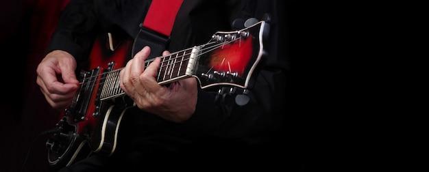 ギタリストの手と黒いテーブルの上のギターがクローズアップ。エレクトリックギターを弾く。スペースをコピーします。