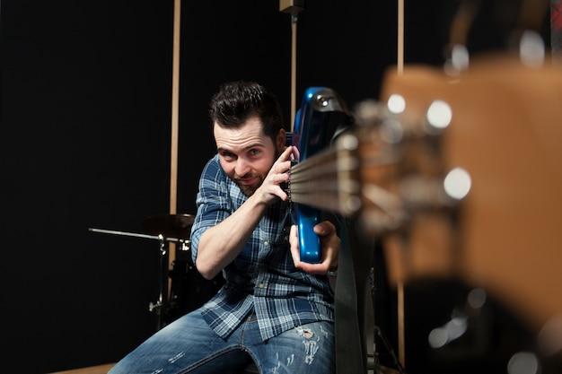 Guitarist holding guitar towards camera