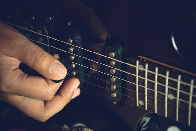 Гитарист репетирует, играя черные винтажные электрогитары. рука крупного плана держит выбор и кладет его на гитару