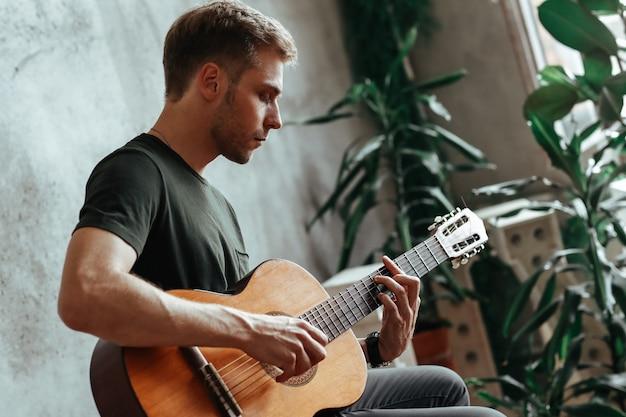 Guitarist man playing guitar at home
