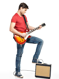 Guitarist man plays on electric guitar with bright emotions, isolate on white