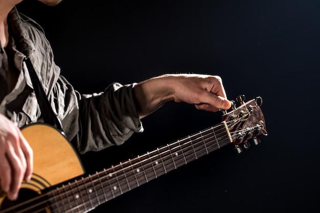 ギタリスト、音楽。若い男は、孤立した黒地にアコースティックギターを演奏します。先のとがった光
