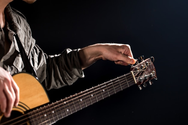 Guitarist, music. a young man plays an acoustic guitar on a black isolated background. pointed light
