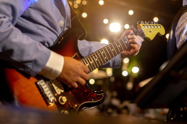 Гитарист играет музыку в ночное время.