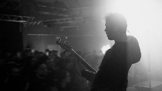 Гитарист играет на электрогитаре в рок-концерте