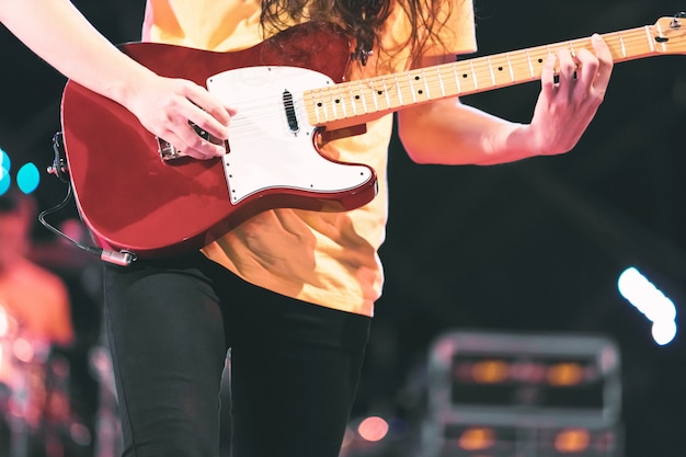 Guitarist playing electricity guitar on concert stage. enterment and music concept.