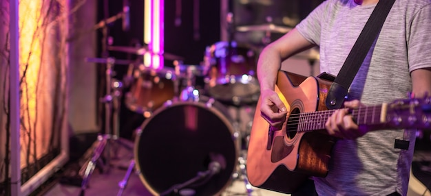 드럼 키트와 함께 뮤지션 리허설을 위해 방에서 연주하는 기타리스트. 음악적 창의성과 쇼 비즈니스의 개념. 프리미엄 사진
