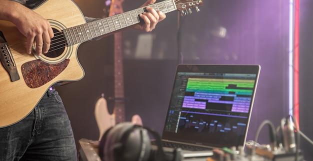 기타리스트는 녹음 스튜디오에서 어쿠스틱 기타를 연주합니다. 흐리게 스튜디오 배경에 사운드 트랙 노트북 모니터.