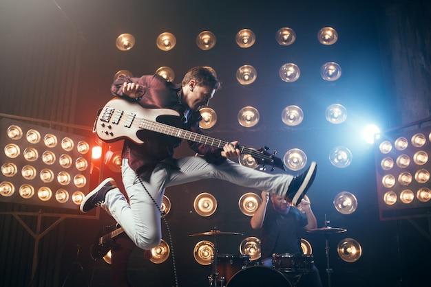 Гитарист играет на бас-гитаре, снимок в прыжке