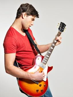 기타리스트는 회색 배경에 밝은 감정으로 일렉트릭 기타를 연주합니다.