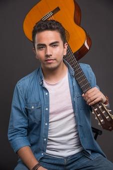 Гитарист позирует с гитарой на темном фоне.