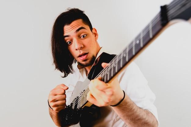 彼のエレクトリックギター、白い背景でポーズのギタリスト。