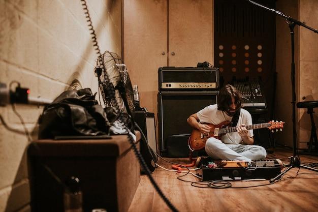 Chitarrista che registra musica rock in studio, seduto sul pavimento