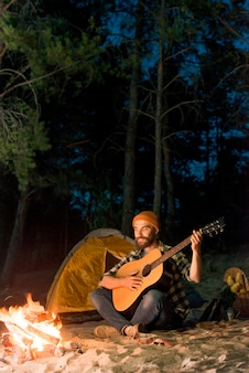 Guitarist singing at night by a tent with a campfire