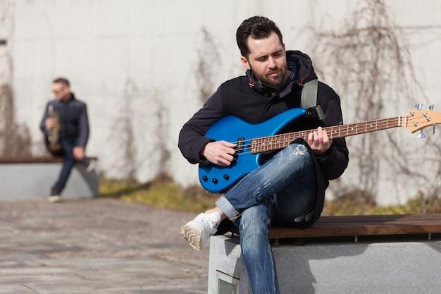 Chitarrista seduto sulla panchina
