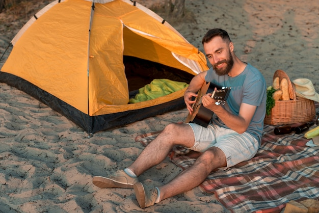 Guitarist sitting next to tent