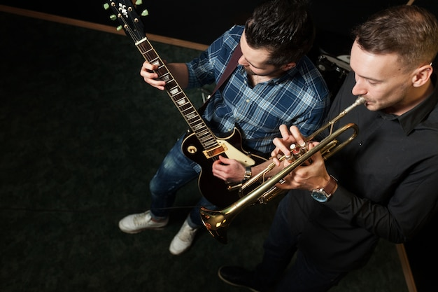Guitarist and trumpet player rehearsing in studio