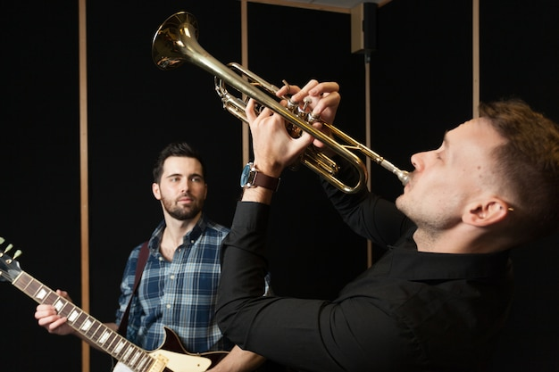 Guitarist watching trumpet player