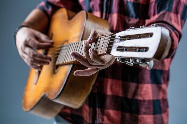 ギターと弦。アコースティックギターを手に持ってギターを弾く男。音楽のコンセプト。ギタリストが演奏します。ギターを弾く。パブに座っている流行に敏感な男。ライブ音楽