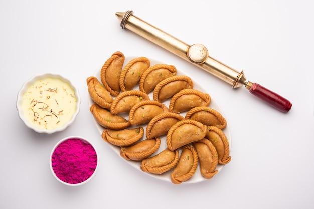 グジヤまたはグジアまたはカランジ。ホーリー祭とディワリ祭の間に作られた甘い餃子を皿に盛り付けます