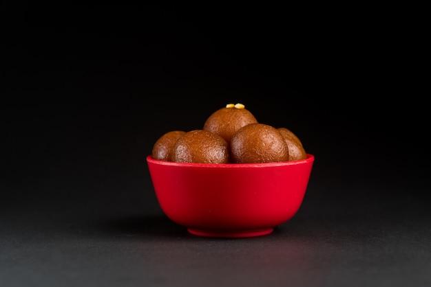 Gulab jamun in bowl on black background. indian dessert or sweet dish.