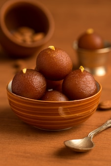 Gulab jamun in bowl and copper antique bowl with spoon. indian dessert or sweet dish.