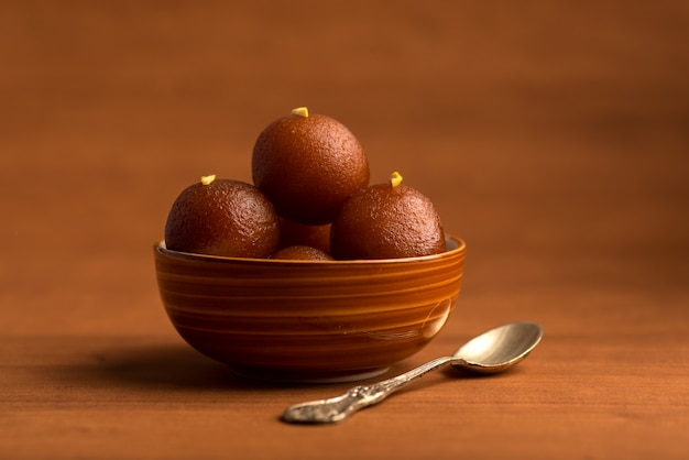 Gulab jamun in bowl on wooden table. indian dessert or sweet dish.