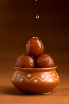 Gulab jamun in clay pot. indian dessert or sweet dish