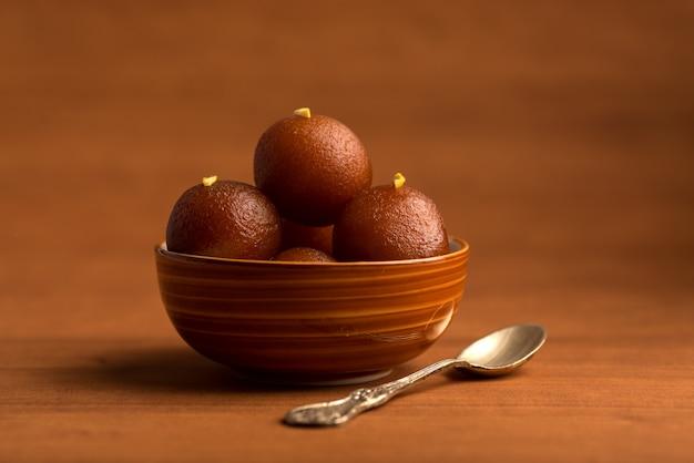 木製のテーブルの上にボウルにgulab jamun。インドのデザートまたは甘い料理。