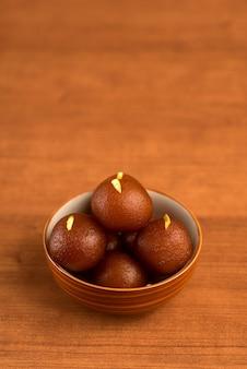 나무 테이블에 그릇에 gulab jamun. 인도 디저트 또는 달콤한 요리.