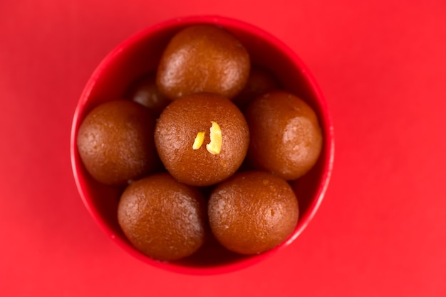 Gulab jamun in red bowl on red background. indian dessert or sweet dish.
