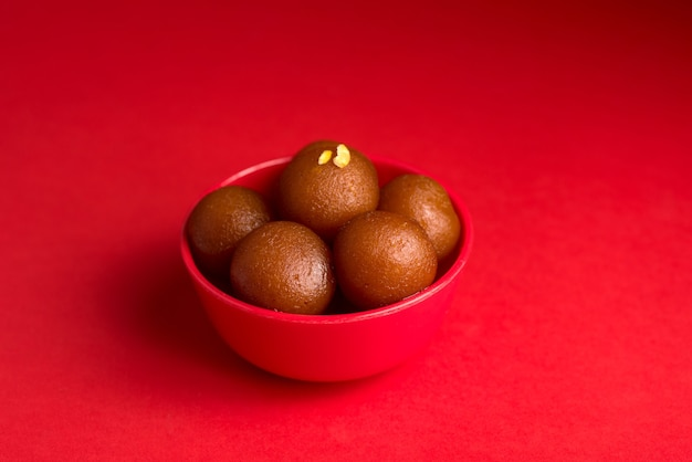 Gulab jamun in red bowl on red table. indian dessert or sweet dish.