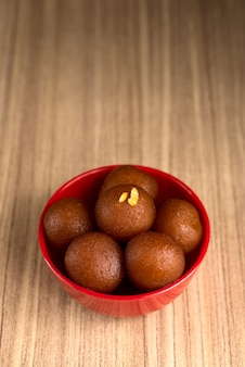 Gulab jamun in red bowl on wooden background. indian dessert or sweet dish.