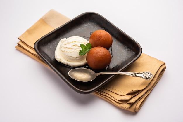 グラブジャムンの伝統的なインドのデザートにバニラアイスクリームを添えて