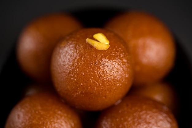 黒い背景にボウルにgulab jamun。インドのデザートまたは甘い料理。