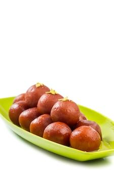 インドのデザートgulab jamun。白い表面上に分離されて甘い料理