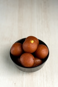 インドのデザートや甘い料理:木製のテーブルの上にボウルにgulab jamun。