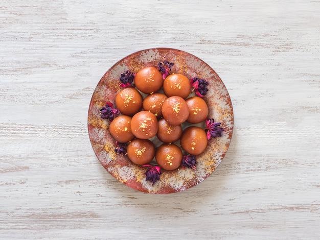 Gulab jamun-白い木製のテーブルに伝統的なインドのお菓子