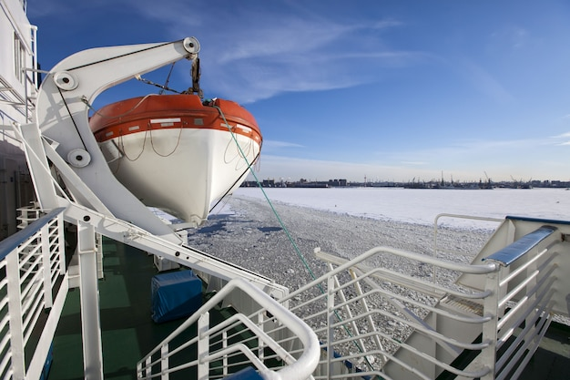 Gulf of finland covered with ice on st. petersburg seaport and a lifeboat from a vessel in the foreground. russia