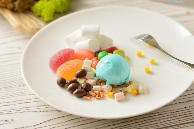 白いプレートにキャンディーとマシュマロの装飾が施されたガム風味のアイスクリームボール