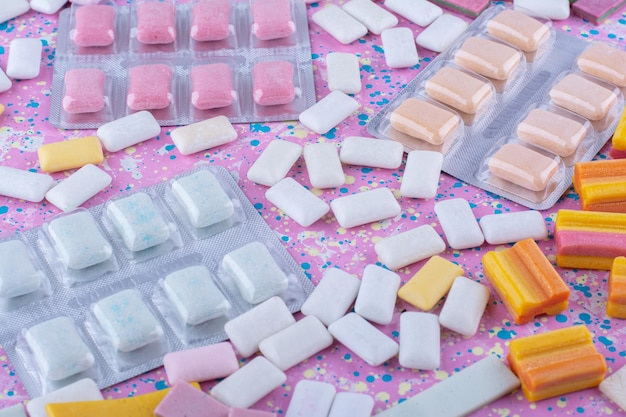 Пакеты жевательной резинки на разноцветной поверхности разбросаны среди кусочков жевательной резинки.