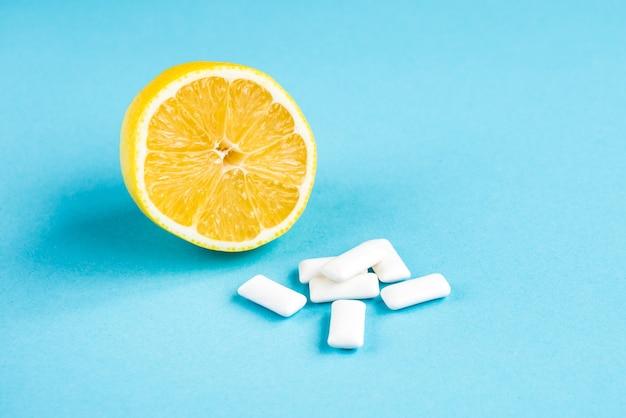 Gum with lemon on blue background.