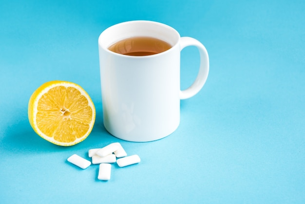 Gum with lemon and mug of tea on blue background. cleaning and protection teeth.