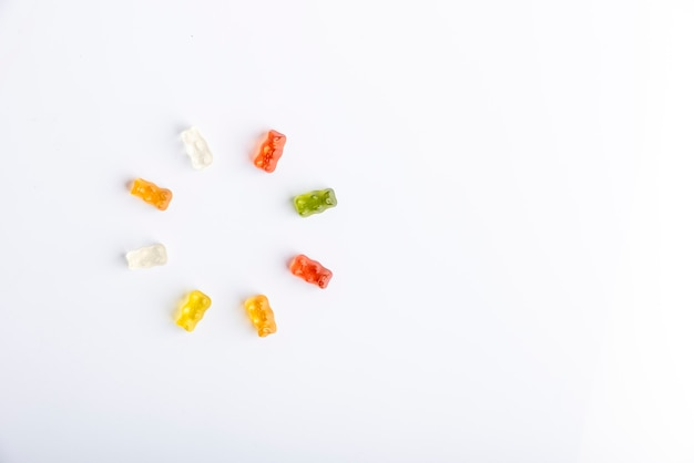 Gummy bears in circle, different colors on white background