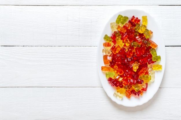 Мармеладные мишки в тарелке яркие желейные конфеты, витаминные добавки вид сверху copy space
