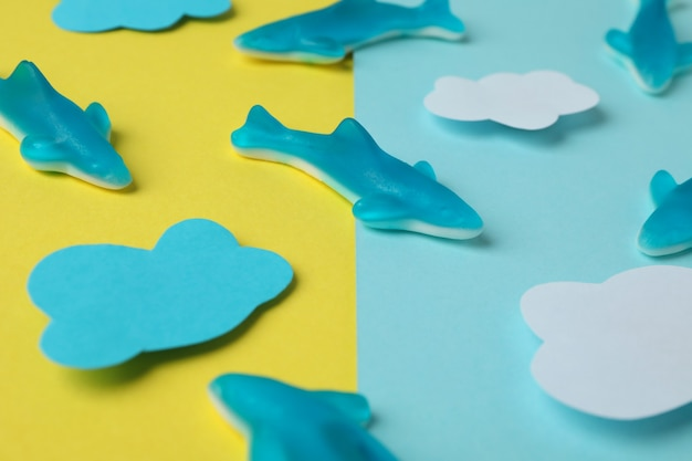 Gummy candies in the form of whale and decorative clouds on two tone background.