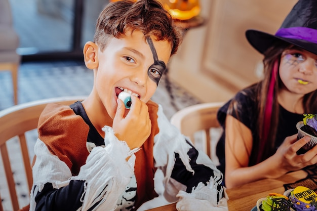 Gummy eye. handsome dark-eyed boy wearing pirate suit for halloween feeling excited while eating gummy eye
