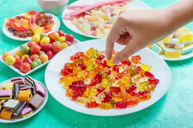 테이블에 젤리 젤리 감초 사탕 손은 접시에서 다채로운 젤리 곰을 가져옵니다