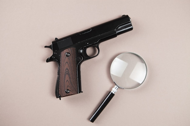테이블에 총과 돋보기. 조사 개념